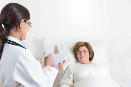 Standing Doctor writes prescription to Senior Patient lying in bed Stock Photo - 12793311
