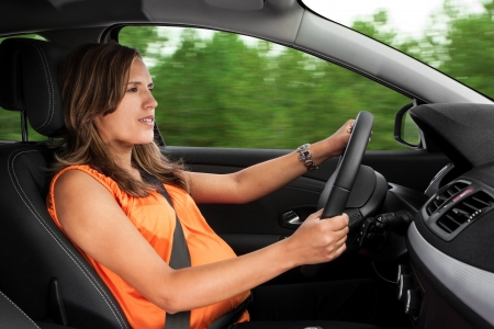 Pregnant Woman Driving a Car Through the Woods Stock Photo