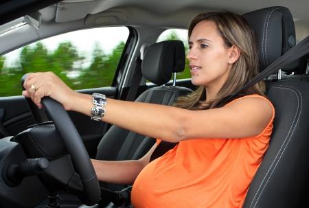 conducci�n: Mujer embarazada que conduce un coche por el bosque