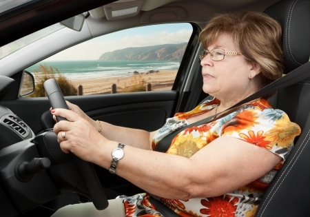 Senior Woman Driving a Car Through the Beach Road Stock Photo