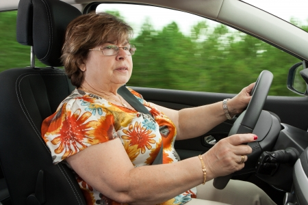 car driving: Senior Woman Driving a Car Through the woods Stock Photo