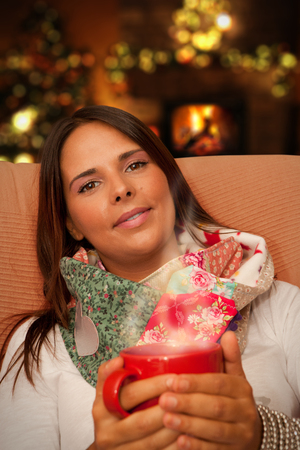 Woman having Hot Drink during Christmas night seating at her home waiting for presents photo