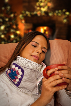 Woman holding Hot Drink during Christmas night seating at her home waiting for presents photo