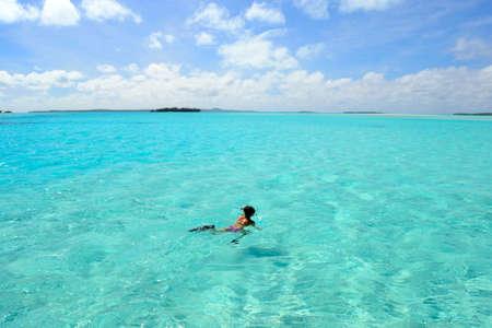One person snorkeling in the turquoise Aitutaki lagoon