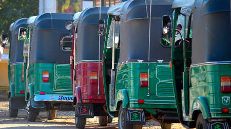 A red motorickshaw amongst green ones at Anuradhapura bus stand, Sri Lanka Stock Photo - 16205474