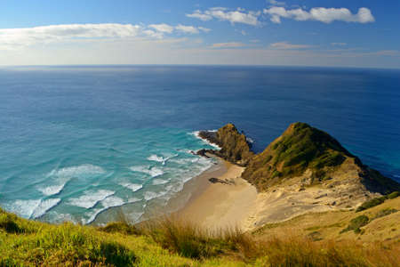 The lonely beach of Cape Reinga  New Zealand - Far North , where Tasman Sea  left  meets Pacific Ocean  right  - august 2011  Stock Photo