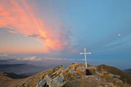 A stunning cloudscape at dusk from the top of a mountain at 2150 m a m s l  near Turin  Italy , with the christian cross and a little moon on the right  photo