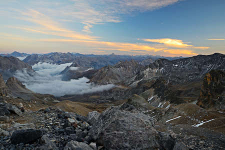 View from a high mountain trail taken at 3000 m just after sunset during the descend from Mount Thabor, italian-french Alps