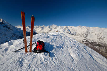 On the top of the mountain, pair of back country - tour ski and a backpack with avalanche safety tools  Scenic high mountain background  Gran Paradiso peak, 4061 m   Stock Photo