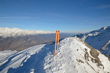 Wide angle view of a pair of back country ski on the top of the mountain in a clear bright day and scenic winter background  photo