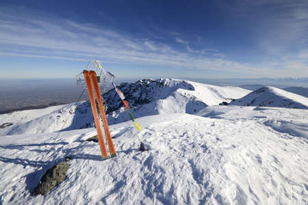Pair of back country ski, the cross of the top and buddhist flags in the wind, in scenic winter wide angle landscape  photo