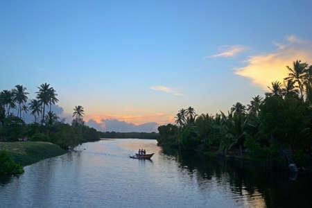Wonderful sunset on Tangalla backwaters, Sri Lanka  Blurred motion boat on the river  Stock Photo