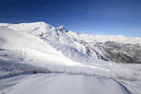 cuneo province: Wide angle view of the alpine arc in Piedmont, Italy, with powder snow in the foreground Stock Photo