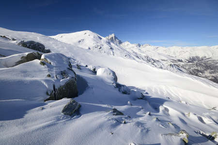 Wide angle view of the alpine arc in Piedmont, Italy, with windswept snowdrift and boulders in the foreground Stock Photo - 17512351