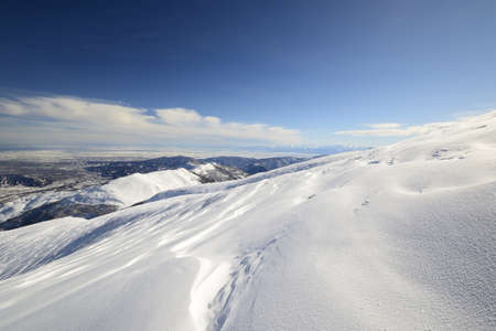 Wide angle view of the alpine arc in Piedmont, Italy, with windswept snowdrift in the foreground Stock Photo - 17512345