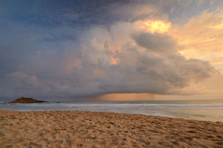 Like an atomic explosion, clouds gathering at the horizon at dusk taken by a double exposure shot from the tropical beach of Mirissa, Sri Lanka, during monsoon time Stock Photo - 17610323