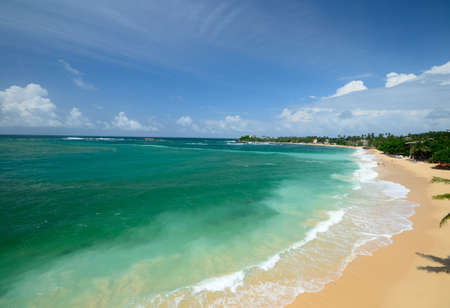 Tropical beach in monsoon season and rough turquoise ocean, Unawatuna, Sri Lanka Stock Photo