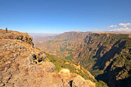 Wide angle view from the Simien Mountain National Park in the dry season with armed ranger on the ridge
