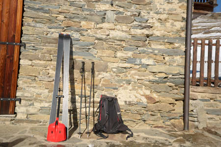 non moving activity: Pair of tour ski with backpack and light shovel for avalanche rescue on an old stone wall in the italian Alps