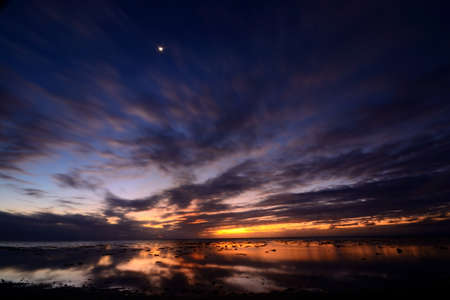 Blurred cloudscape and seascape at dusk, long exposure taken on Aitutaki lagoon during low tide, Cook Islands  photo