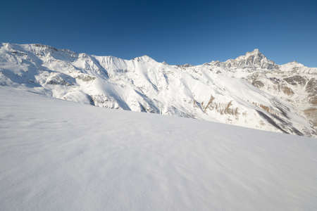 Panoramic view of high mountain range with the majestic M  Viso  3841 m  in the background and snowy slope in the foreground