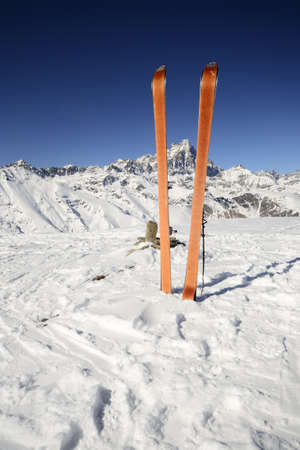 Pair of back country ski  with orange climbing skin  on the summit with superb view of the majestic Monte Viso  3841 m  in the background  photo