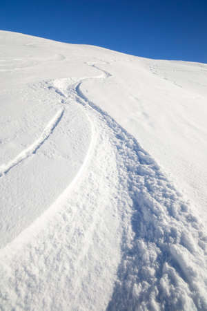 off piste: Deep zigzag shaped ski track on off piste candid slope covered by powder snow in a bright sunny day