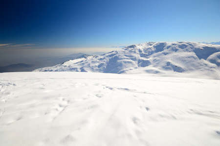 Wide angle view of candid snowy slope in scenic background overlooking the foggy valleys below  photo
