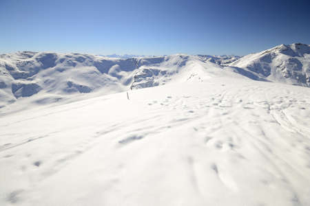 Scenic view of the alpine arc from the smooth summit ridge with powder snow and soft back country ski tracks in the foreground  Stock Photo - 18102701