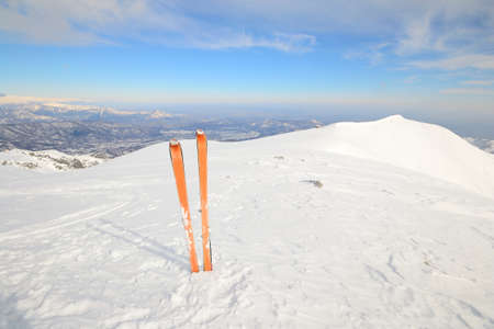 Pair of back country ski  with orange climbing skin or sealskin  on the summit with superb view of the valleys below  Stock Photo