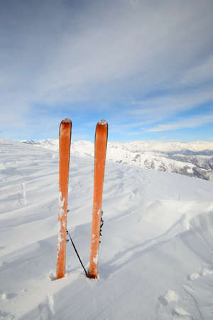 Pair of back country ski  with orange climbing skin or sealskin  on the summit with superb view of the valleys below  photo