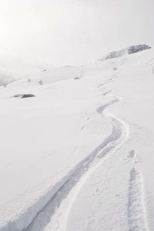 deep powder snow: Deep zigzag shaped ski track on off piste candid slope covered by powder snow in a cloudy day  Stock Photo