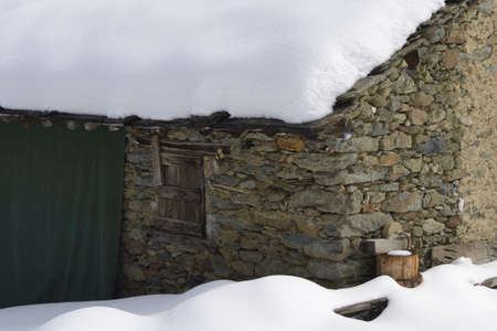 Old pasture hut in scenic winter landscape, italian Alps photo