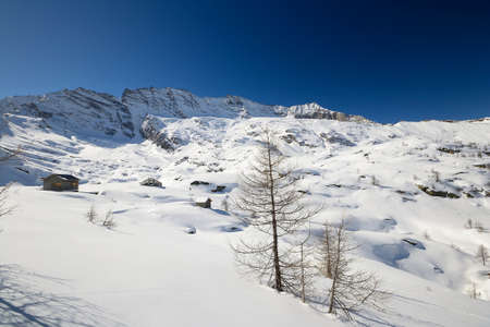 Candid snowy slope with alpine huts in scenic background of high mountain peaks  M  Levanna, 3600 m  in the Gran Paradiso National Park  Location  italian Alps, Piedmont Stock Photo - 18690825