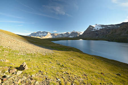 High altitude mountain range and lake illuminated by afternoon light, with green pasture in foreground and high peak with glaciers in background  Location  Italian Alps at 2800 m in Gran Paradiso National Park  photo