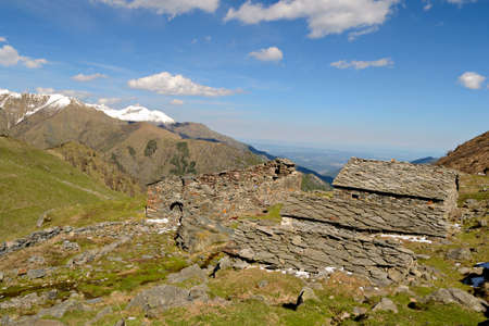 Stone alpine pasture and shepherd s huts, abandoned, weathered and ruined in amazing mountain scenery in spring season  Location  Gran Paradiso National Park, western Alps, Italy  photo