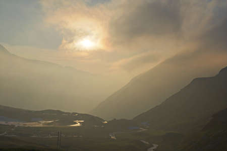 High altitude alpine valley at sunset in stormy weather  Location  western Alps, Torino Province, Italy  photo