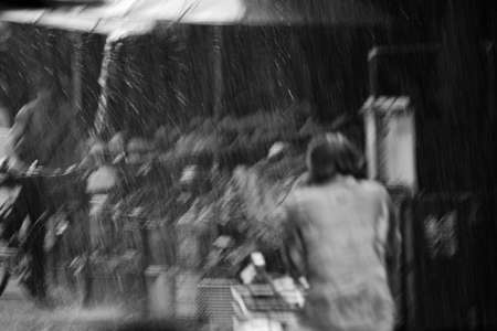 Motion blur astract of bike riders in the main market of Mae Sod, Northern Thailand, under torrential rain in monsoon time