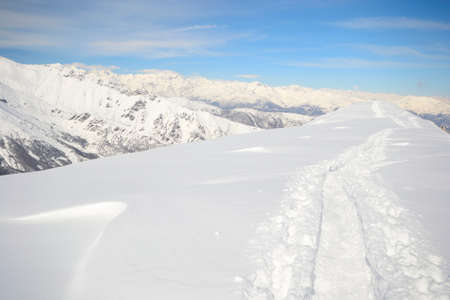 deep powder snow: Alpinist hiking uphill by ski touring on the mountain ridge in powder snow with deep track in the foreground and scenic high mountain view in the background