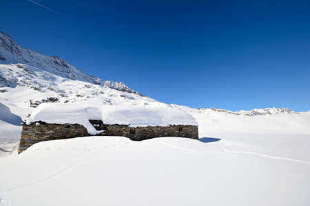 Winter landscape in the italian Alps with abandoned pasture hut covered by snow  Back country ski tracks  photo
