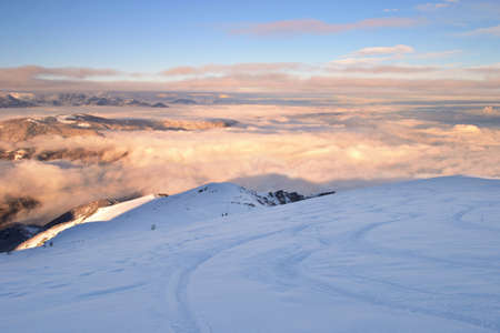 Ski touring tracks  back country ski tracks  in foggy landscape at sunset, italian Alps  photo
