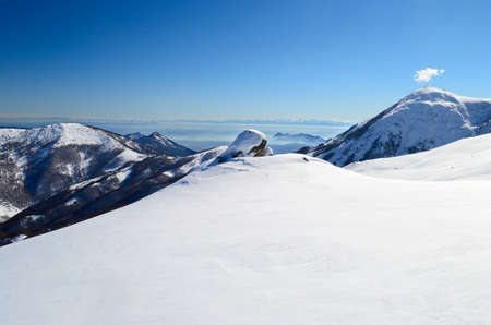 Snowy slope with superb panoramic view of mountain peaks, valleys and plain. Piedmont, Italian Alps. photo