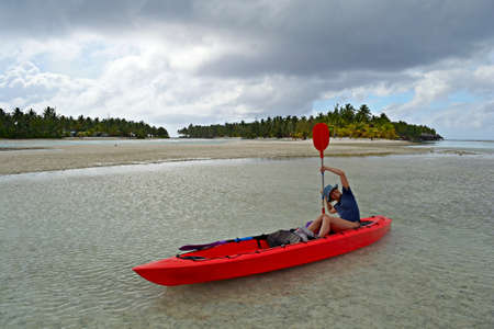 Exploring the gorgeous lagoon of Aitutaki by canoeing  Tropical stormy weather at the horizon  Woman handling paddle  Location  Cook Islands Stock Photo