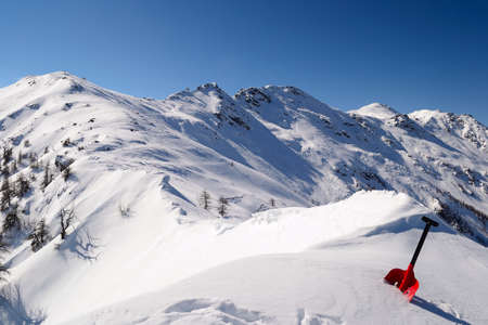 On the top of the mountain, avalanche shovel in the snow in scenic high mountain background  photo