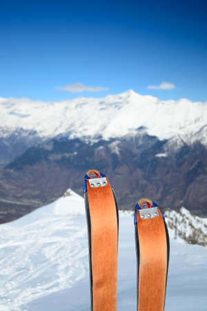 Selective focus on back country ski with orange sealskin attached in scenic alpine backgrounds photo