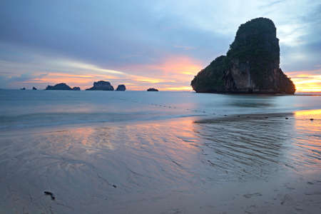 Low tide with a vibrant colored sunset in the majestic scenery of Railey Bay, Krabi, Southern Thailand  Blurred motion, very long exposure