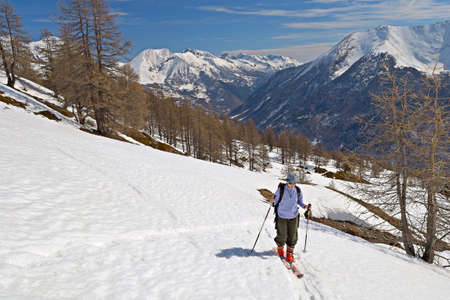 Tour skier hiking uphill under a bright sun in spring. photo