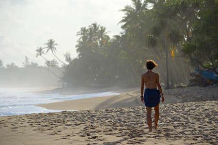 Woman walking on tropical beach at sunset, Tangalla, Sri Lanka