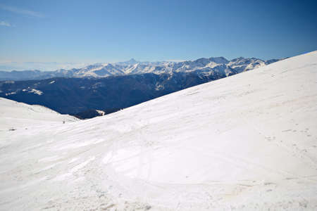 Infinite panoramic view from a snowy slope in spring with foggy valleys below. Unrecognizable tour skier. photo