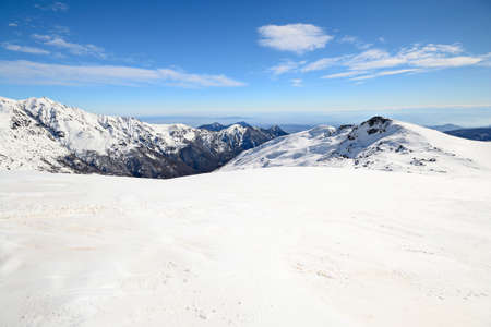 Infinite panoramic view from a snowy slope in spring with foggy valleys below. photo